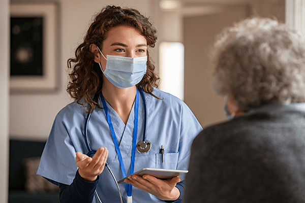 masked female health care worker talks to senior patient